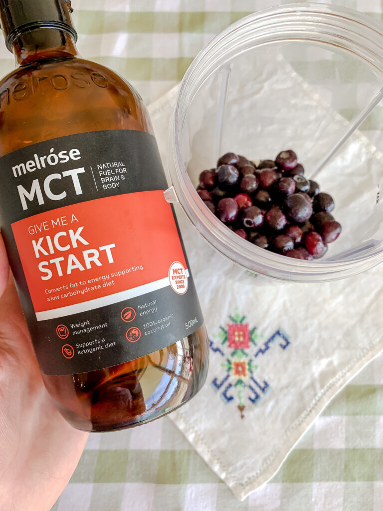 mct oil in a bottle next to berries