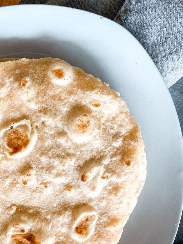 Bubbly soft sourdough tortilla on vintage blue plate
