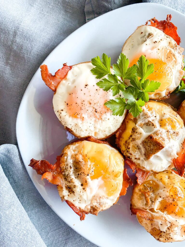Grab and Go breakfast muffins with crispy bacon and soft eggs sunny side up.