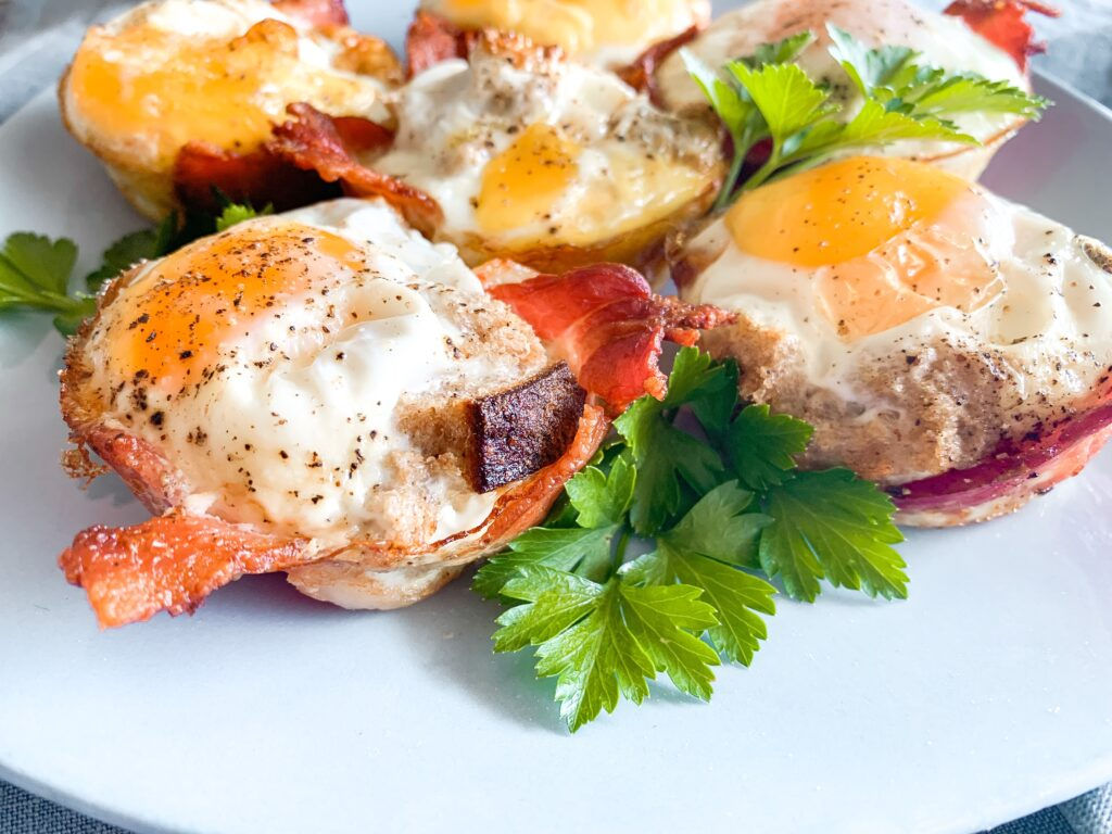Grab and Go breakfast muffins with crispy bacon and soft eggs sunny side up on vintage blue plate