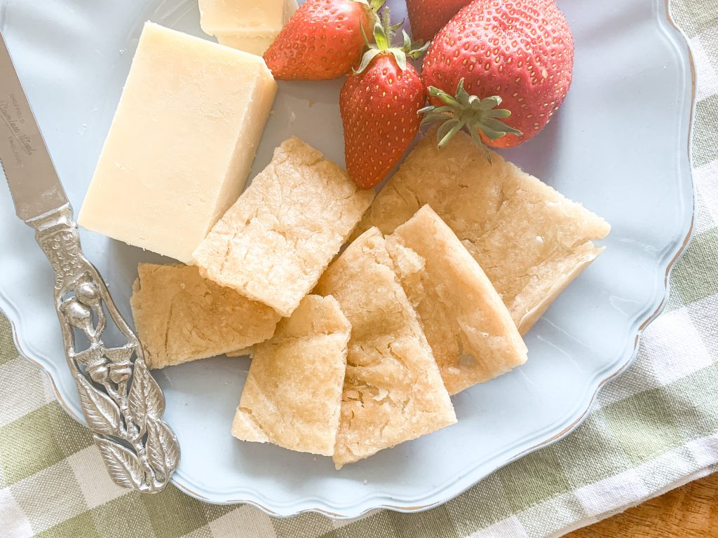 Simple and Cripsy sourdough crackers on a vintage Australia blue plate with a gum leaf cheese knife and home grown strawberries